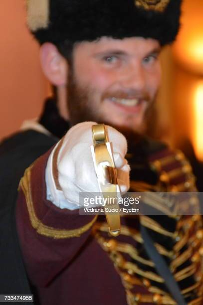 Portrait Of Smiling British Royal Guard Holding Sword