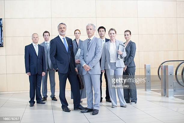 Portrait of smiling business people at bottom of escalator
