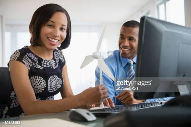 Portrait of smiling business people with wind turbine at computer