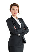 Portrait of smiling business woman with folded hands isolated on white background. Female wearing grey formal suit standing with her arms crossed. Business lifestyle and success concept