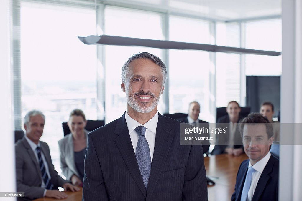 Portrait of smiling businessman and co-workers in conference room : Stock Photo