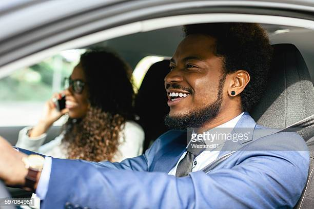 Portrait of smiling businessman driving in a car with his colleague