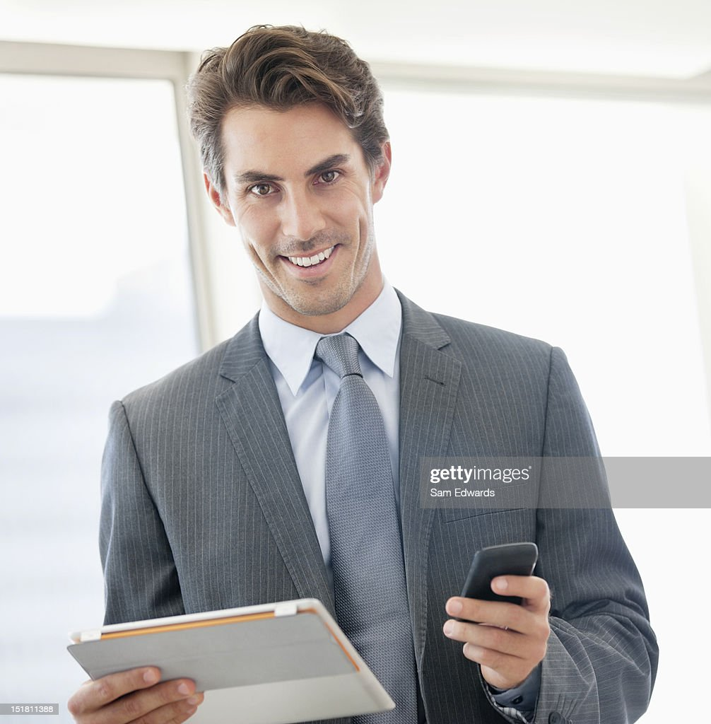 Portrait of smiling businessman holding cell phone and digital tablet : Stock Photo