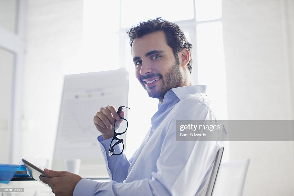 Portrait of smiling businessman holding eyeglasses and digital tablet in office : Stock Photo
