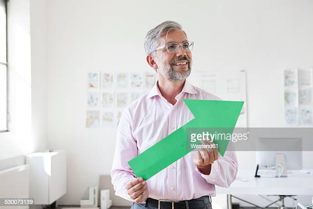 Portrait of smiling businessman holding green arrow