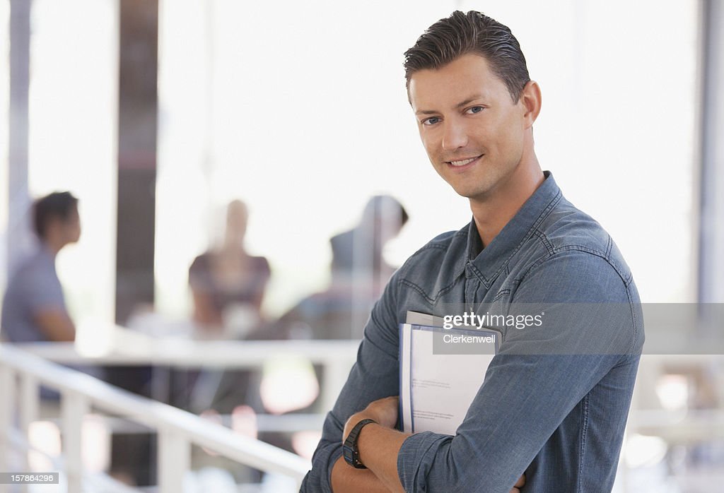 Portrait of smiling businessman holding paperwork in office : Stock Photo