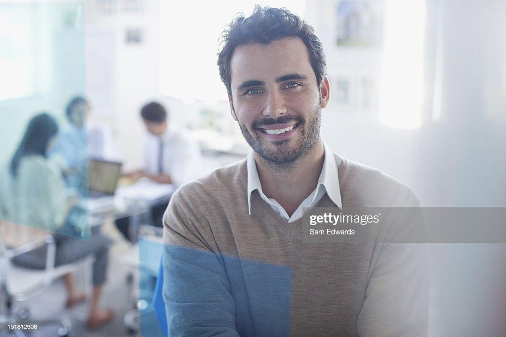 Portrait of smiling businessman in conference room with co-workers in background : Stock Photo