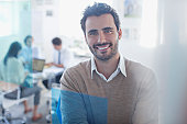 Portrait of smiling businessman in conference room with co-workers in background