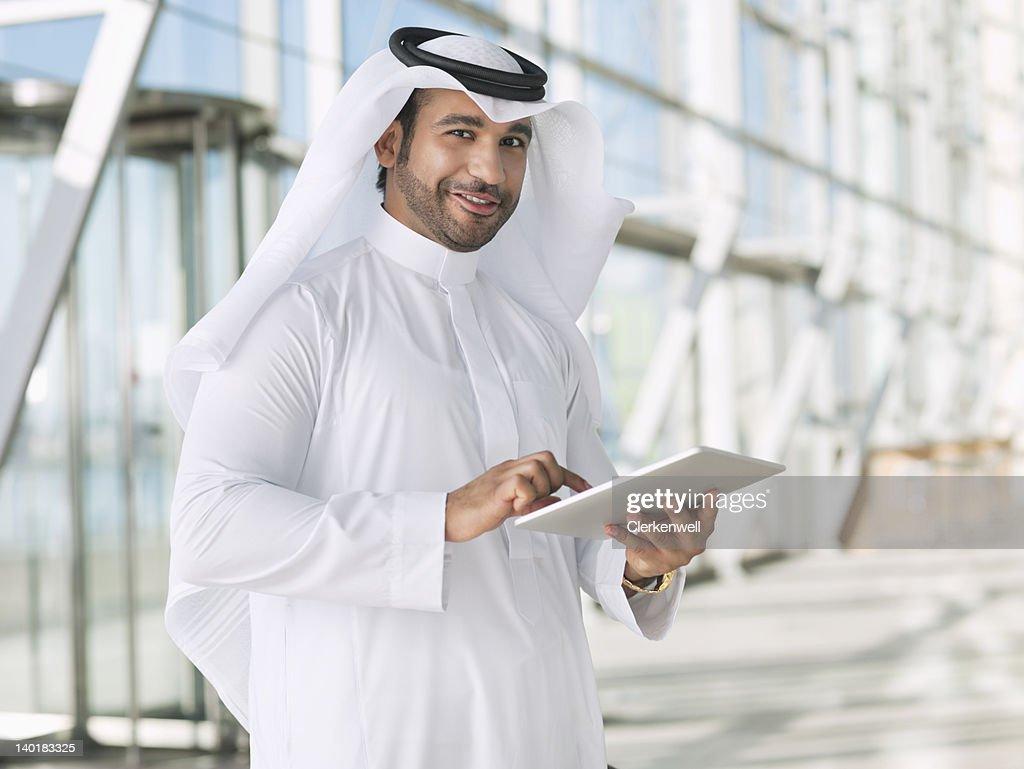 Portrait of smiling businessman in kaffiyeh using digital tablet