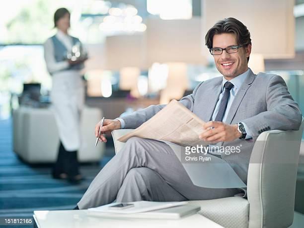 Ritratto di sorridente Uomo d'affari leggendo giornali nella lounge