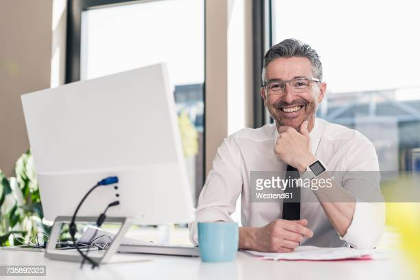 Portrait of smiling businessman sitting at desk in his office