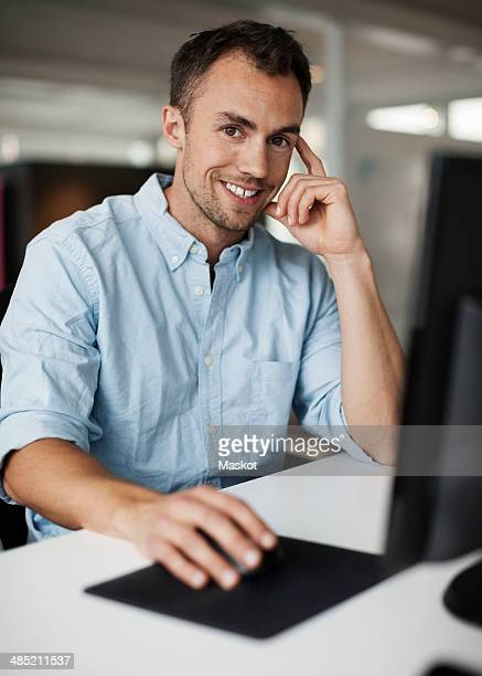 Portrait of smiling businessman using computer in office