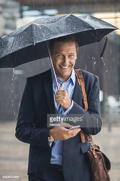 Portrait of smiling businessman using smart phone in city during rainy season