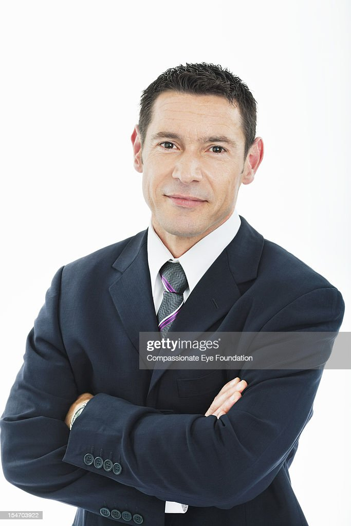 Portrait of smiling businessman with arms folded : Stock Photo