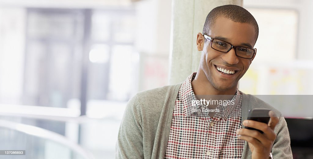 Portrait of smiling businessman with cell phone : Stock Photo