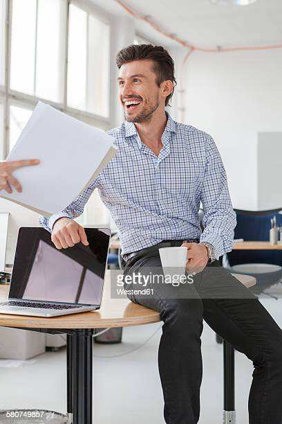Portrait of smiling businessman with coffee cup in an office
