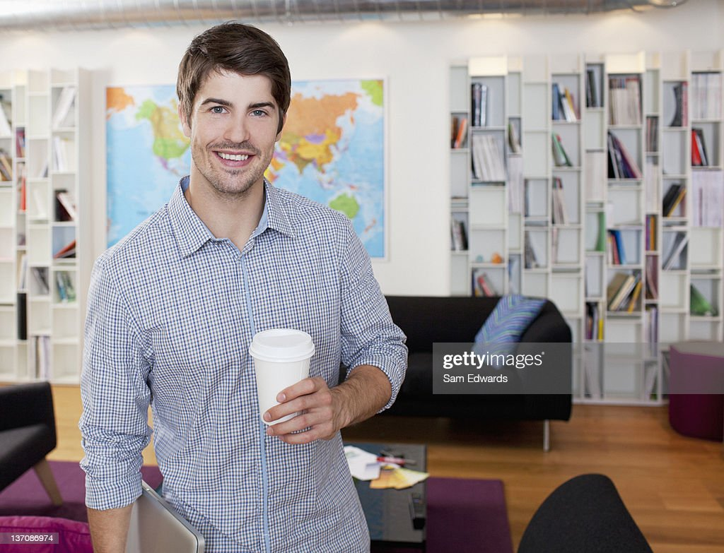 Portrait of smiling businessman with coffee cup in office : Stock Photo