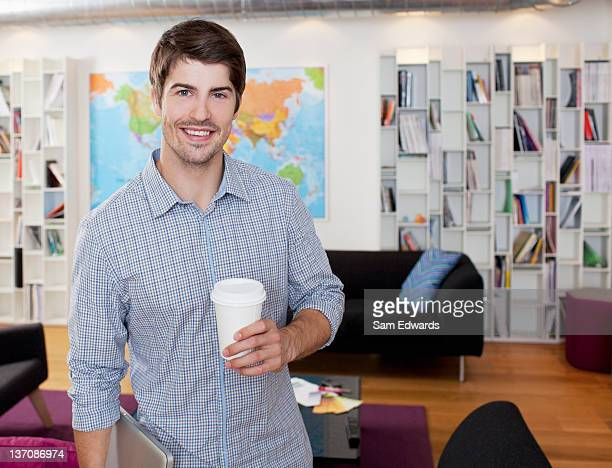 Portrait of smiling businessman with coffee cup in office