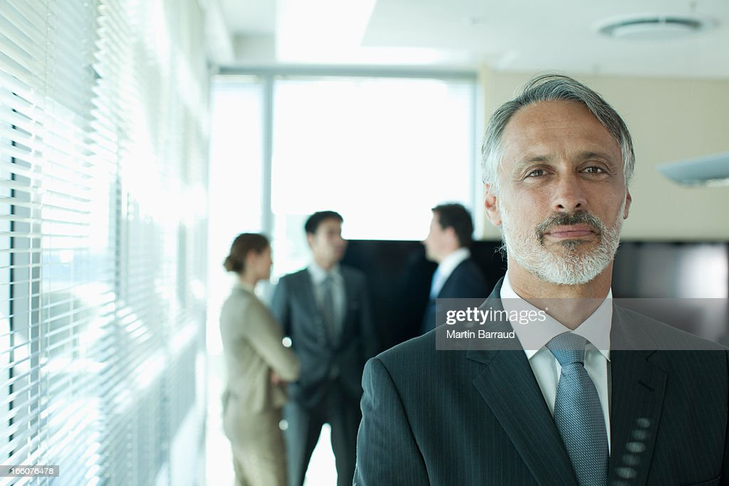 Portrait of smiling businessman with co-workers in background : Stock Photo