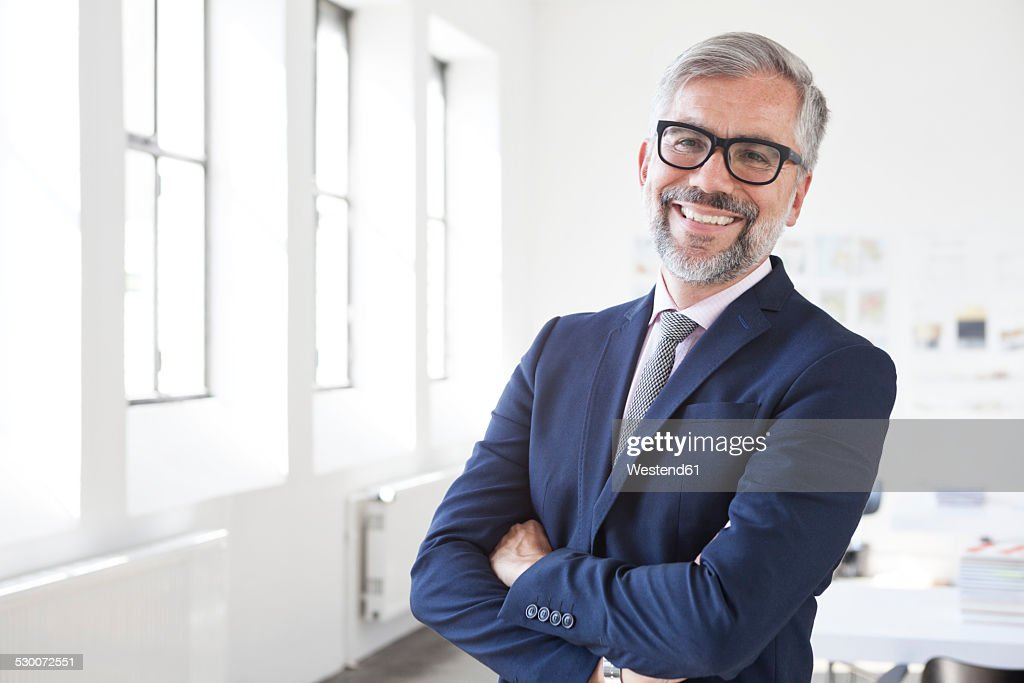 Portrait of smiling businessman with crossed arms in an office : Stock-Foto