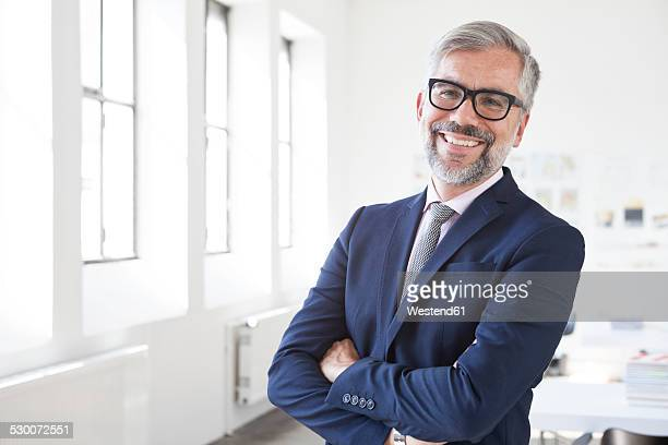Portrait of smiling businessman with crossed arms in an office