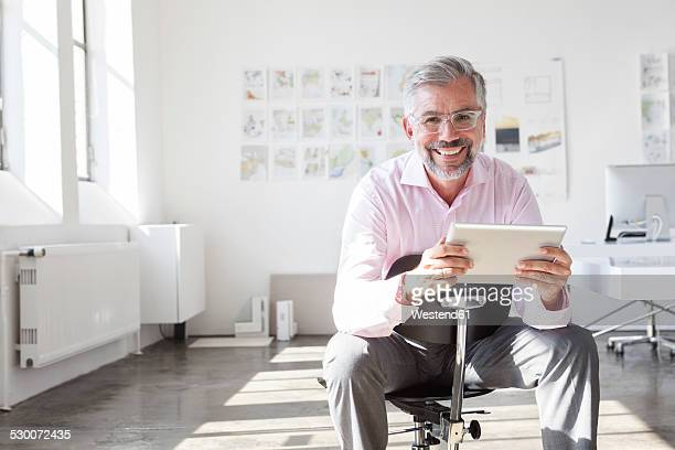Portrait of smiling businessman with digital tablet in an office