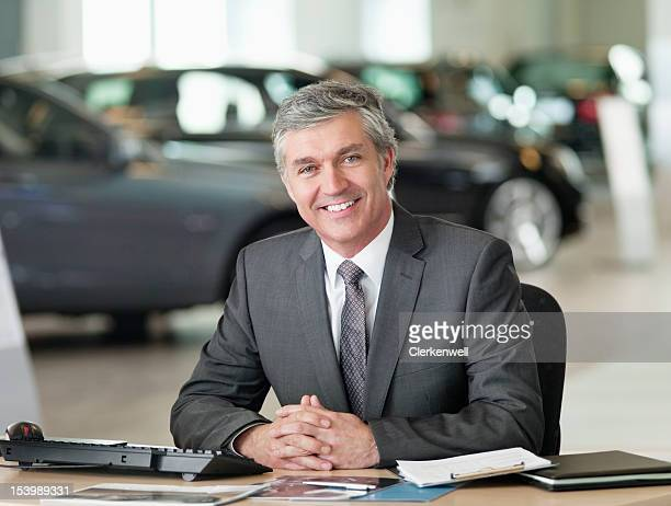 Portrait of smiling businessman with hands clasped at desk in car dealership showroom