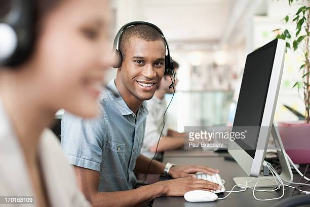 Portrait of smiling businessman with headset at computer in office