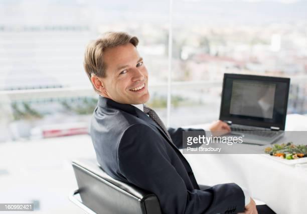 Porträt von lächelnd Geschäftsmann mit laptop und Mittagessen