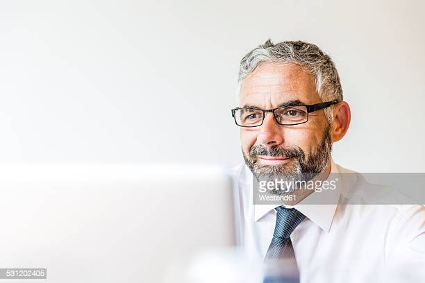 Portrait of smiling businessman working at laptop