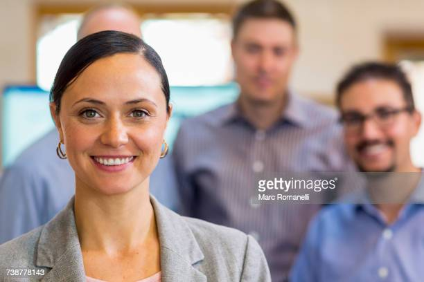 Portrait of smiling businesswoman and team