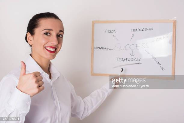 Portrait Of Smiling Businesswoman Gesturing Thumb Up While Pointing On Whiteboard At Office