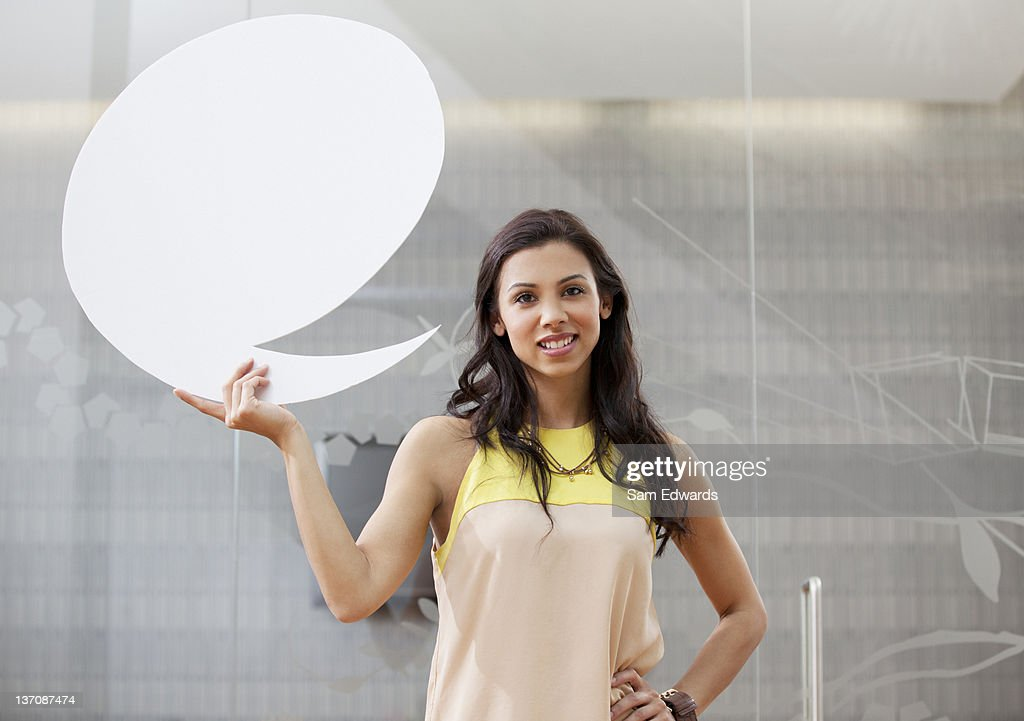 Portrait of smiling businesswoman holding speech bubble