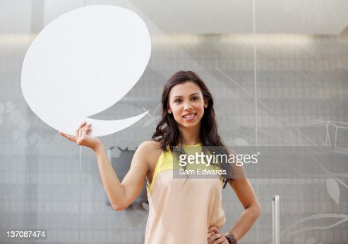 Portrait of smiling businesswoman holding speech bubble : Stock Photo