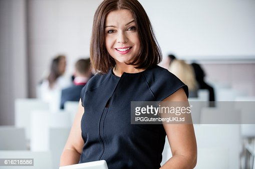 Portrait of smiling businesswoman standing in seminar hall : Photo