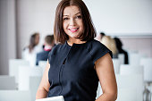 Portrait of smiling businesswoman standing in seminar hall