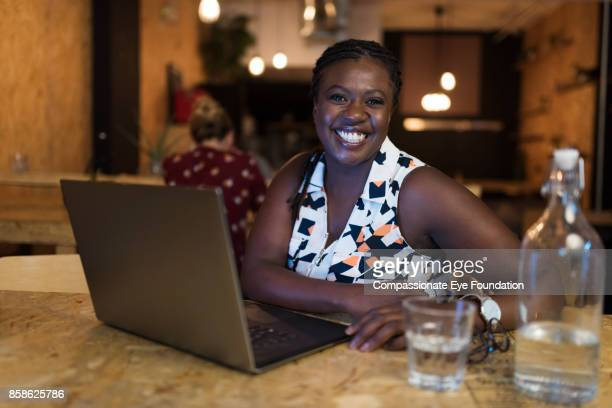Portrait of smiling businesswoman using laptop in cafe