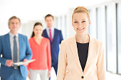 Portrait of smiling businesswoman with colleagues in background at office