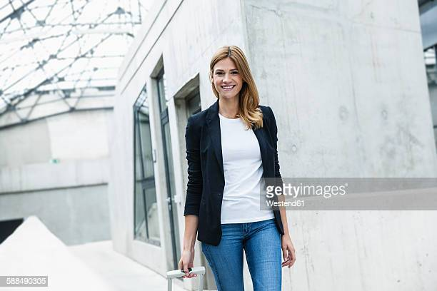 Portrait of smiling businesswoman with luggage