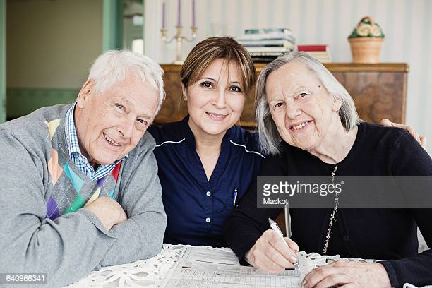 Portrait of smiling caretaker and senior people solving crossword puzzle at nursing home