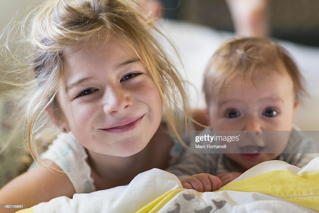 Portrait of smiling Caucasian girl with baby brother