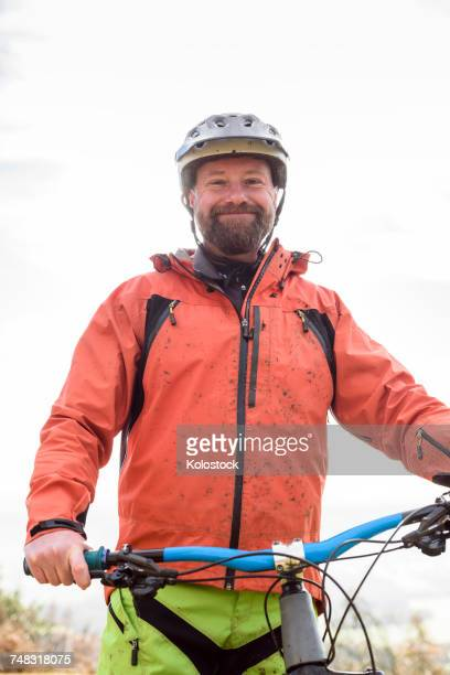 Portrait of smiling Caucasian man splattered in mud holding bicycle