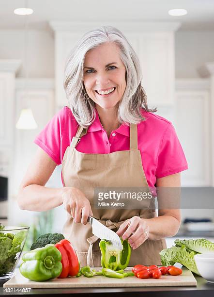 Portrait of smiling Caucasian woman slicing vegetables