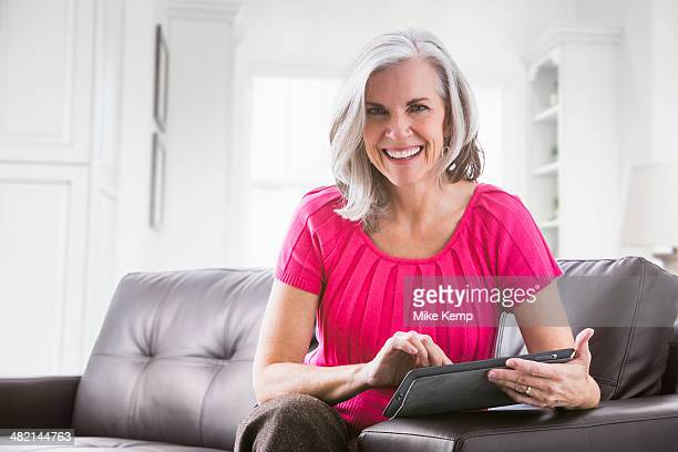 Portrait of smiling Caucasian woman using digital tablet on sofa