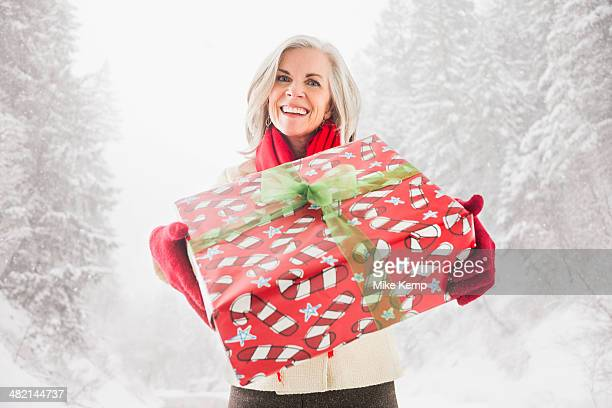 Portrait of smiling Caucasian woman with Christmas gift