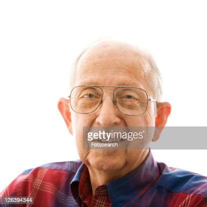 Portrait of smiling Caucasion elderly man in a plaid shirt and glasses.