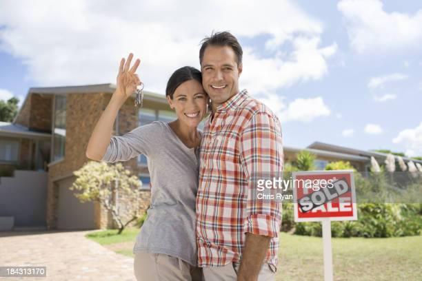 Retrato de casal sorridente segurando as chaves na frente de casa nova