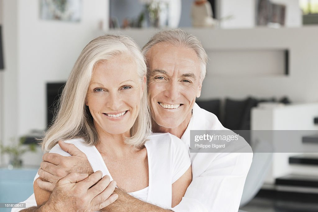 Portrait of smiling couple hugging in living room : Stock Photo