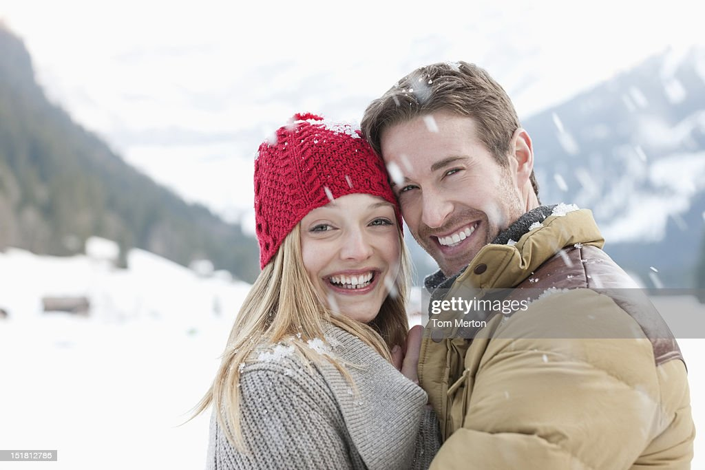 Portrait of smiling couple hugging in snow : Stock Photo