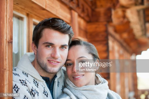 Portrait of smiling couple hugging on cabin porch : Stock Photo